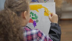 Drawing process: in the artist`s art Studio, hand girl with a brush painting on canvas. Children`s hand of the artist. Gaining paint on the brush, sitting at stock footage