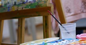 Drawing process: in the artist`s art Studio, hand girl with a brush painting on canvas. Children`s hand of the artist stock footage
