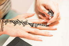 Drawing process of henna menhdi ornament on woman's hand Stock Photo