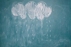 Drawing of rain falling from cloud on chalkboard royalty free stock image