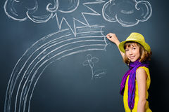 Drawing a rainbow. Joyful pretty girl in colorful clothes drawing a rainbow on a blackboard. Happy childhood Stock Photo