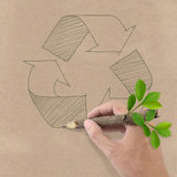 Drawing recycle symbol on Brown Recycled Paper. Male hand drawing recycle symbol on Brown Recycled Paper Stock Photos