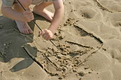 Drawing in the Sand. Kid crouching down on the beach and drawing pictures in the sand with a stick Royalty Free Stock Image