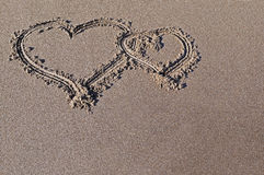 Drawing on sand. Two hearts drawn on sea sand Stock Images