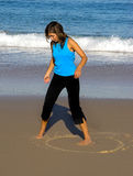 Drawing in the sand. Beautiful woman make drawings in the sand royalty free stock photo