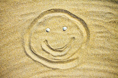 Drawing in the sand on the beach, smiling man Stock Image