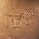 Drawing on the sand of a house and a tree royalty free stock photos