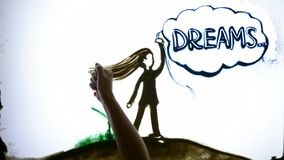 Drawing sand, Man hands write word dreams next to girl from sand on screen. Word dreams Drawing sand, Man hands write message next to girl from sand on screen stock video