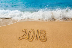Drawing in sand by ocean of 2018 word Stock Photography