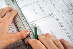 Drawing a skecth. Hand with ruler and pencil writing on blueprint Stock Photos