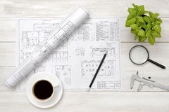 Drawing sketches, magnifier, cup of coffee and houseplant are on wooden surface Royalty Free Stock Photography