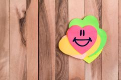 Cute heart smile emoji. Drawing smile emoji in heart shaped sticky note on wood background stock photos