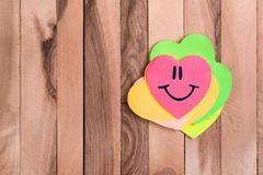 Cute heart smile emoji. Drawing smile emoji in heart shaped sticky note on wood background stock photo