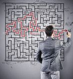 Drawing the solution. Businessman drawing the solution of a difficult maze Royalty Free Stock Photos