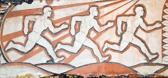 Drawing of the Soviet era on the wall. Running athletes. Permission to shoot is not required, the picture is applied to the destro Stock Photography