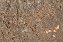 Drawing on a stone. Petroglyph ancient man on the rock Royalty Free Stock Photo