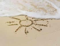 Drawing of sun in the sand on exotic beach Stock Image