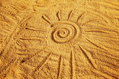 Drawing of a sun symbol on the golden sand at the seashore Royalty Free Stock Photo