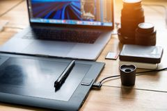 Drawing tablet and laptop computer, harddisk, memory card, camera lens on table. Photographer concept stock images