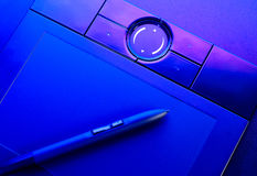 Drawing tablet with pen in blue light Stock Images