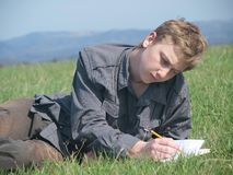 Drawing teenager. Portrait of young blond man writing or drawing on the blank paper (wearing grey shirt) laying in the grass in the sun Royalty Free Stock Image