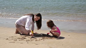 Drawing together in the sand stock footage