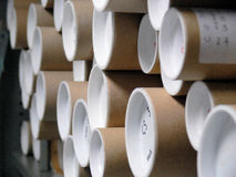 Drawing tubes. Cardboard drawing tubes with white end caps, stored horizontally royalty free stock image