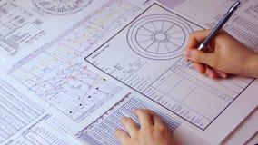 Drawing up an astrological forecast. Astrological forecast. Astrologer make horoscope data sheet using data astrologocal ephemeris spreadsheet stock video footage