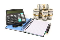 Drawing up a budget. Notebook, pen, calculator and dollars banknotes  with soft shadow over white background Stock Image