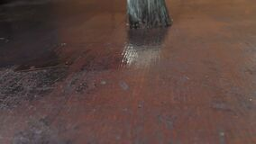 Drawing of a varnish by a brush on looking old wooden surface. Repairing of furniture stock footage