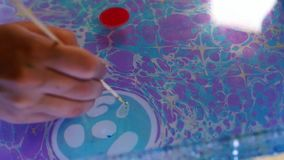 Drawing on the water. Painter is drawing on the water. Drawing on the water. Colored paint splashes on water. Creative abstract background close-up. Painter is stock video footage