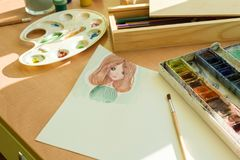 Drawing by watercolor - anime girl, on a table with watercolor paint brush.  royalty free stock image
