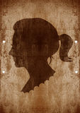 Drawing of a woman face. In old-fashioned silhouette style on grunge background Royalty Free Stock Image