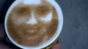 Drawing of a woman`s face on a foam coffee latte