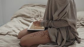 Drawing woman using tablet. Female artist using digital tablet for drawing. She is sitting in bed and using stylus. Henna on her leg. Lovely interior stock footage