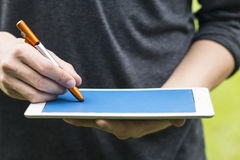 Drawing and Writing with pen on touch Tablet. Man drawing and Writing with pen on touch Tablet Stock Image