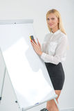 Drawing and writings on a flipchart. Beautiful business woman en Royalty Free Stock Photo