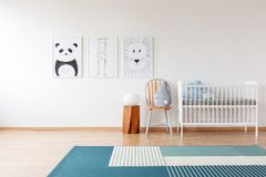 Drawings in bright child`s room. Pillow on chair between wooden stool and white crib in bright child`s room with blue carpet and drawings Royalty Free Stock Images