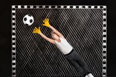 Boy goalkeeper catches a football.Drawings in chalk on the wall. Drawings in chalk on the wall.Boy goalkeeper catches a football stock images