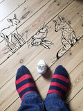 Drawings on floor with animals and Easter. Drawings of aninmals on wooden floor. Bambi, fox and rabbit drawn on the floor, animals look towards the egg. Head of Royalty Free Stock Photo