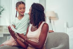 Cheerful Afro-American mom hugging daughter and looking at her drawings. Drawings in hands. Cheerful dark-haired appealing arresting Afro-American mom hugging stock images