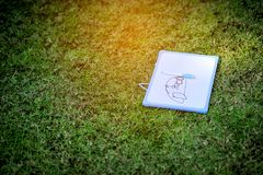 The drawings of the little child. Drawings of cute little kids are placed in the lawn stock photos