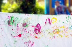 Drawings made by children's hands full of colorful gouache. Children playing making colorful designs with hands dipped in colored dye Stock Photos