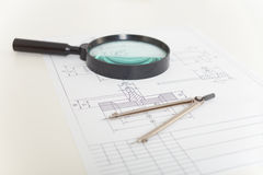Drawings, magnifier and compasses. The drawings, magnifier and compasses on a white table Stock Images
