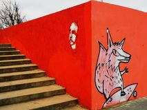 Drawings by original artists for the free theme. Fox on a skateboard and face head red background is bright orange next to the stairs wall angle of the pyramid stock photo