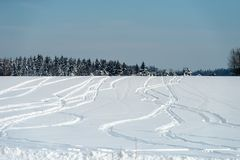 Drawings in the snow. Drawings from snowmobile tracks on a snow-covered field in a winter day Royalty Free Stock Photos