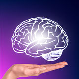Drawn brain hovered over the human hand stock photography