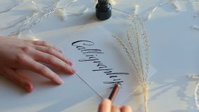 Drawn calligraphy on white paper with nib pen. Written word on white paper with broad nib pen and black ink. Twinkling garlands and yellow twig. Concept of stock footage