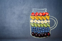 Drawn with chalk jar with rainbow fruit and berries. Toning. selective focus Royalty Free Stock Photography