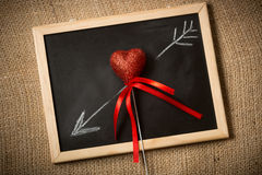 Drawn on chalkboard arrow going through decorative heart Royalty Free Stock Photo